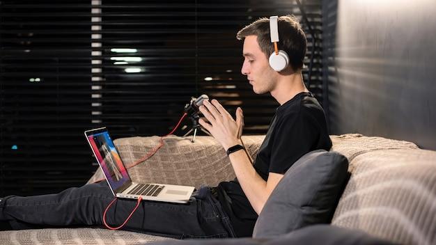 Der junge mann, der inhalte erstellt, sitzt auf seinem laptop auf dem sofa der konferenz. verbundene hände. von zu hause aus arbeiten