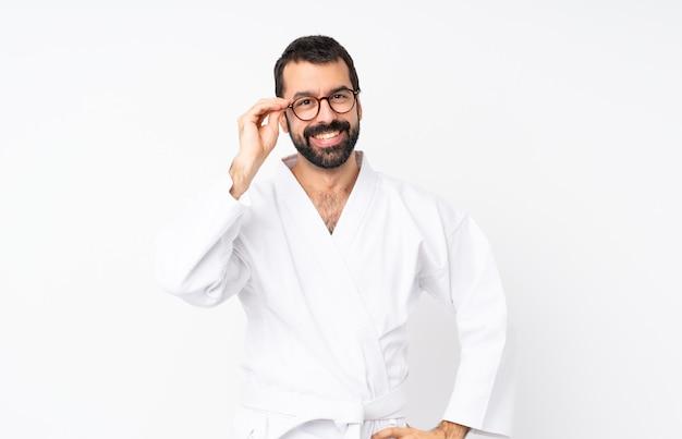 Der junge mann, der karate mit gläsern tut und glücklich
