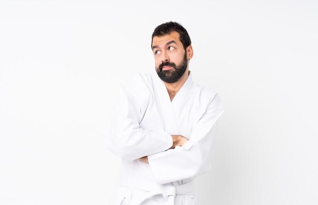 Der junge mann, der karate über lokalisiertem weiß macht zweifel tut, gestikulieren beim anheben der schultern
