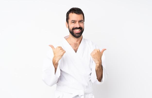 Der junge mann, der karate über lokalisiertem weißem hintergrund mit den daumen tut, up geste und lächeln