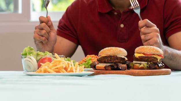 Der junge mann, der messer und gabel hält, ist bereit, einen hamburger zum mittagessen zu essen.