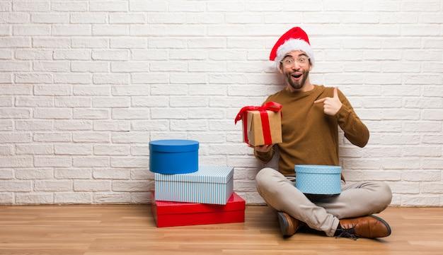 Der junge mann, der mit den geschenken sitzt, die weihnachten überrascht feiern, fühlt sich erfolgreich und wohlhabend