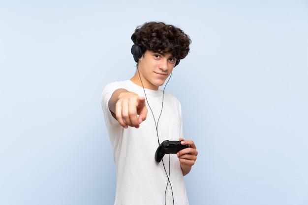 Der junge mann, der mit einem videospielprüfer über lokalisierter blauer wand spielt, zeigt finger auf sie mit einem überzeugten ausdruck