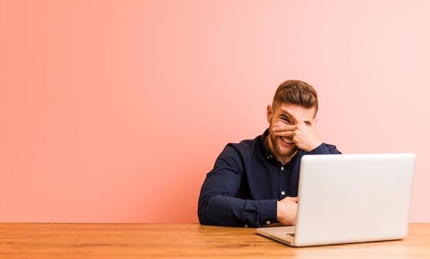 Der junge mann, der mit seinem laptop arbeitet, blinken an der kamera durch finger, verlegenes bedeckungsgesicht.