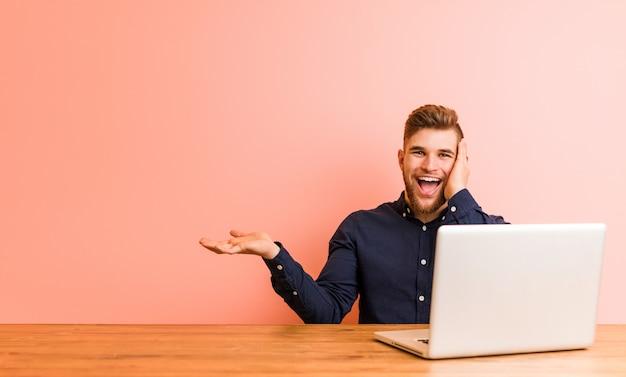 Der junge mann, der mit seinem laptop arbeitet, hält kopienraum auf einer palme, hält hand über backe. erstaunt und entzückt.