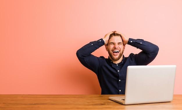 Der junge mann, der mit seinem laptop arbeitet, lacht freudig und hält die hände auf dem kopf. glückskonzept.