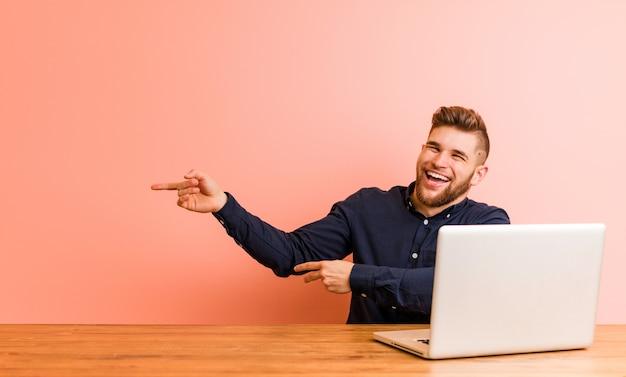 Der junge mann, der mit seinem laptop arbeitet, regte das zeigen mit den zeigefingern weg auf.