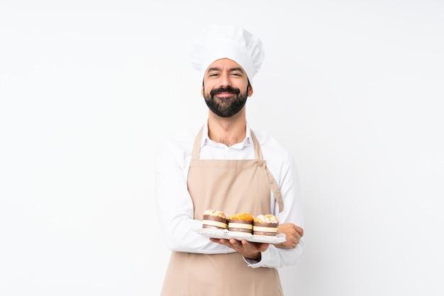 Der junge mann, der muffinkuchen hält, die arme halten, kreuzte in frontaler position
