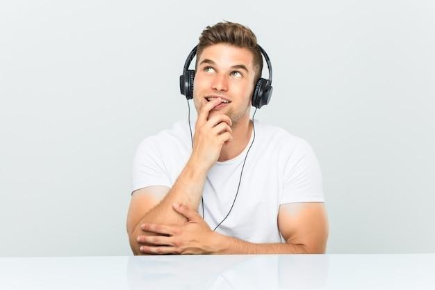 Der junge mann, der musik mit kopfhörern hört, entspannte sich das denken an etwas