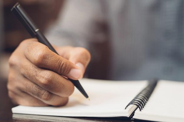 Der junge mann der nahaufnahmehand sitzt mit dem stift, der den notizblock des aufzeichnungsvortrags in das buch auf dem tischholz schreibt.
