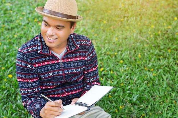 Der junge mann der nahen hand sitzt mit dem stift, der den notizblock des aufzeichnungsvortrags schreibt
