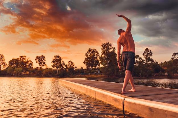 Der junge mann, der pilates tut, trainiert stellung auf hölzerner anlegestelle bei sonnenuntergang