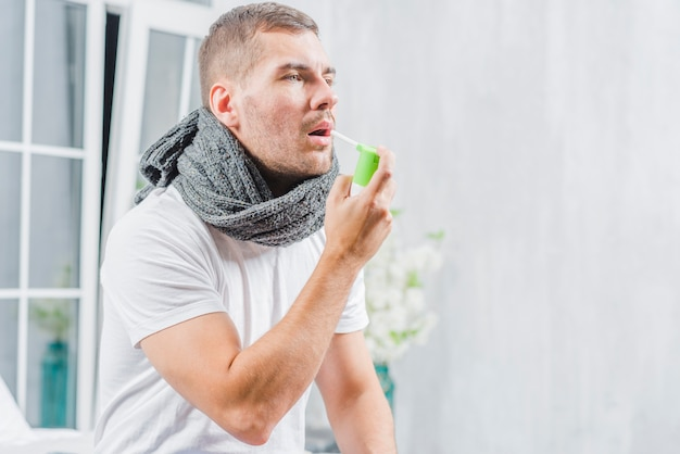Der junge mann, der unter kälte leidet, behandelt ihren hals mit einem spray