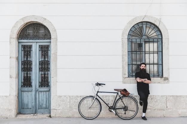 Der junge mann, der vor fenster mit seinem arm steht, kreuzte nahe seinem fahrrad