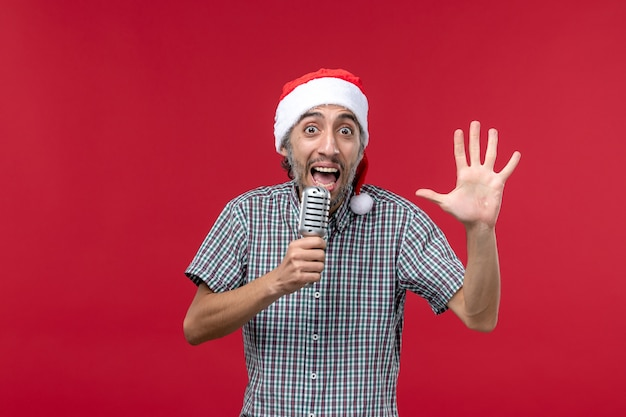 Der junge mann der vorderansicht, der die zahl auf der sängermusik der roten wand-emotionsfeiertage zählt, zählt