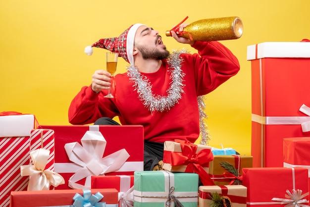 Der junge mann der vorderansicht, der herum sitzt, präsentiert geschenke, die mit champagner auf gelb feiern