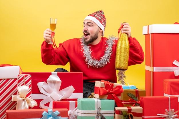Der junge mann der vorderansicht, der herum sitzt, präsentiert mit champagner auf gelbem hintergrund