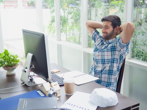 Der junge mann, der zu hause arbeitet und entspannen sich