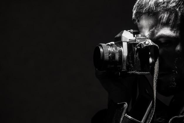 Der junge mann fotografiert ein retro-schwarzweißfoto der alten kamera.
