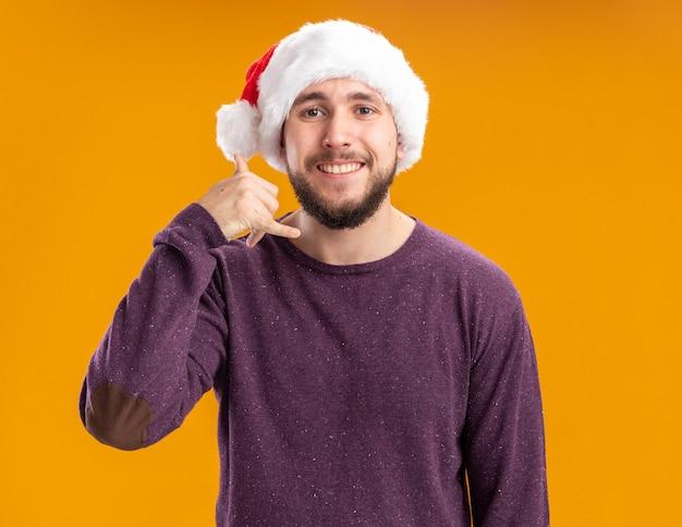 Der junge mann im lila pullover und in der weihnachtsmannmütze, die glücklich und positiv zeigt, nennt mich geste, die über orange wand steht