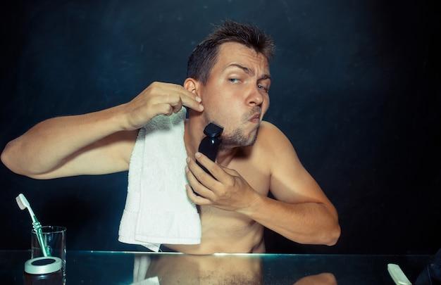 Der junge mann im schlafzimmer sitzt vor dem spiegel und kratzt sich zu hause am bart. konzept der menschlichen emotionen
