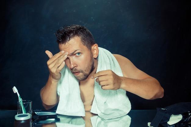 Der junge mann im schlafzimmer sitzt vor dem spiegel und kratzt sich zu hause am bart. konzept menschlicher emotionen und probleme mit haaren