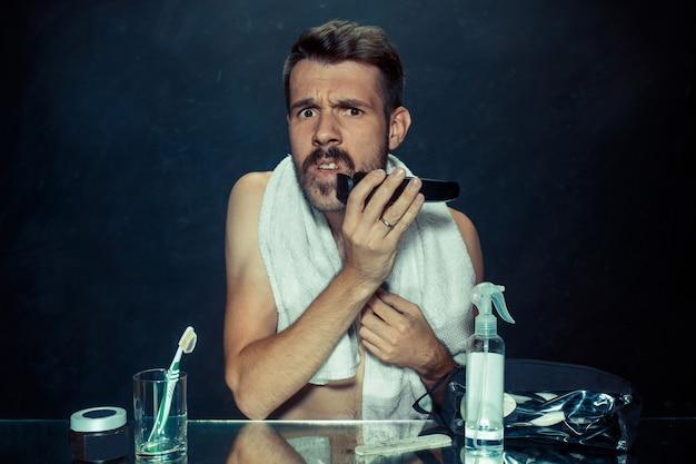 Der junge mann im schlafzimmer sitzt vor dem spiegel und kratzt sich zu hause am bart. menschliche emotionen und lebensstilkonzept