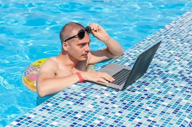 Der junge mann in den sommerferien mit dem laptop, geschäft online. entfernung home office im schwimmbad im gummiring auf quarantäne