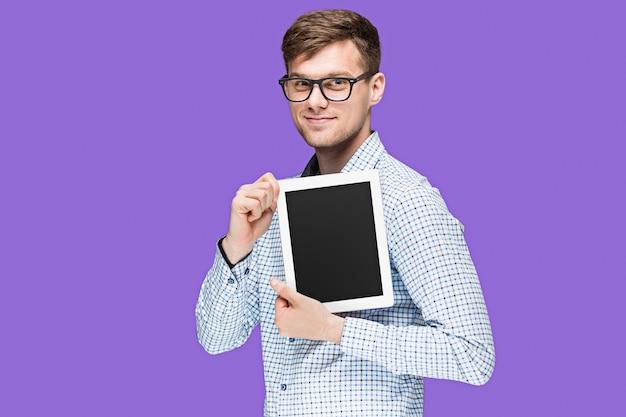 Der junge mann in einem hemd, das an laptop auf lila wand arbeitet