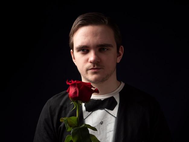 Der junge mann in einem schwarzen t-shirt-anzug, der eine rote rose in den händen hält, sieht mit einem ernsten gesicht auf schwarz aus