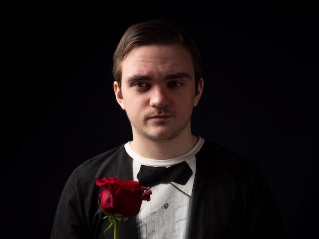Der junge mann in einem schwarzen t-shirt-anzug, der eine rote rose in seinen händen hält, sieht mit einem ernsten gesicht auf einem schwarzen hintergrund aus