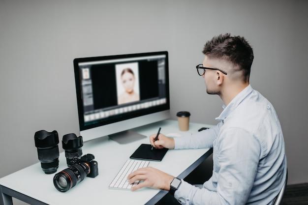Der junge mann ist ein freiberuflicher fotograf, der zu hause an einem computer arbeitet