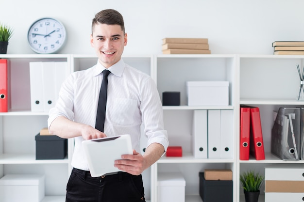 Der junge mann ist im büro und hält eine tablette.