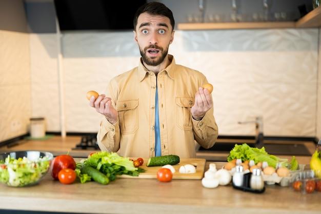 Der junge mann ist neugierig darauf, vegetarischen salat zu kochen. der hübsche mann weiß nicht, was er kochen soll