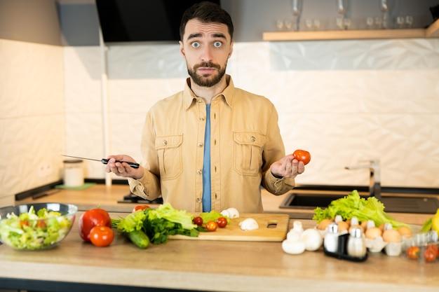 Der junge mann ist neugierig darauf, vegetarisches essen zu kochen. der hübsche mann weiß nicht, was er kochen soll