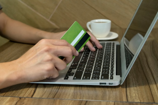Der junge mann kaufte online ein, indem er eine kreditkarte als zahlungsmittel verwendete.