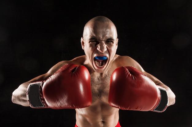 Der junge mann kickboxen auf schwarz mit kapa im mund