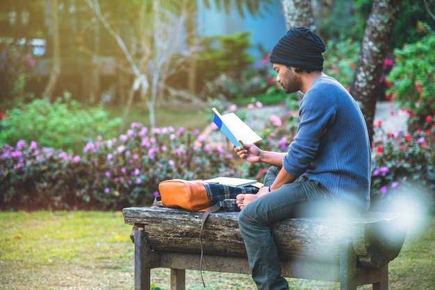 Der junge mann las im park ein buch. unter den natürlichen bäumen und schönen blumengarten