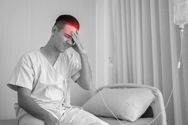 Der junge mann leidet unter kopfschmerzen, drückt die finger an die schläfen und schließt die augen, um die schmerzen mit hilflosem gesichtsausdruck zu lindern