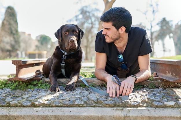 Der junge mann liegt neben seinem labrador retriever in einem park und sieht den hund und den hund an