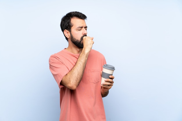 Der junge mann mit dem bart, der einen mitnehmerkaffee über lokalisiertem blau hält, leidet mit husten und dem gefühl schlecht