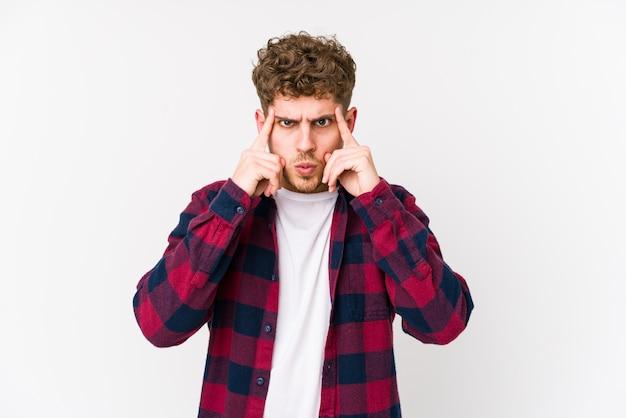 Der junge mann mit dem blonden lockigen haar, der isoliert ist, konzentrierte sich auf eine aufgabe, wobei die zeigefinger den kopf zeigten