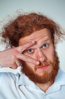 Der junge mann mit den langen roten haaren schaut in die kamera und öffnet das auge