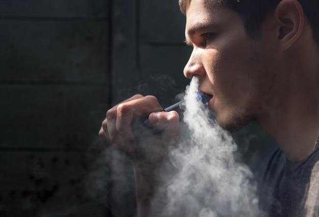 Der junge mann mit der elektronischen zigarette