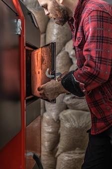 Der junge mann mit festbrennstoffkessel, der mit biobrennstoffen arbeitet, sparsam heizt.