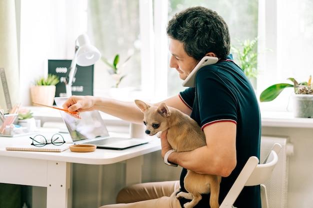 Der junge mann mit hund, der von zu hause aus arbeitet
