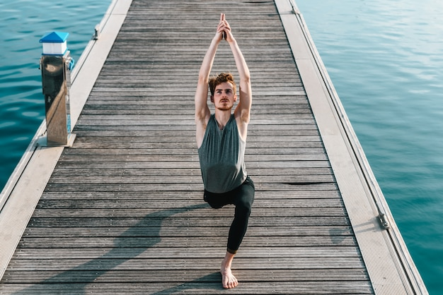 Der junge mann praktiziert yoga, um sich vom stress der stadt zu entspannen und sport zu treiben.