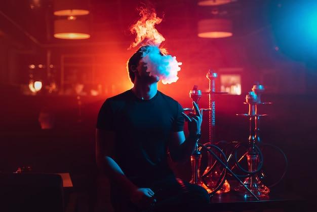 Der junge mann raucht eine shisha und stößt eine rauchwolke aus