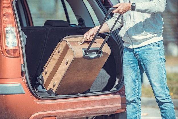 Der junge mann schätzt das gepäck im kofferraum