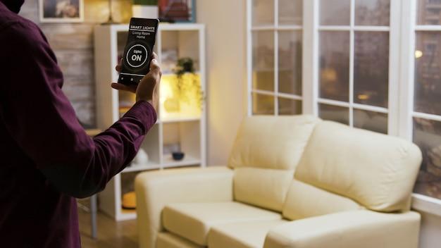 Der junge mann schaltet mit einer intelligenten licht-app das licht im haus ein und setzt sich dann auf das sofa